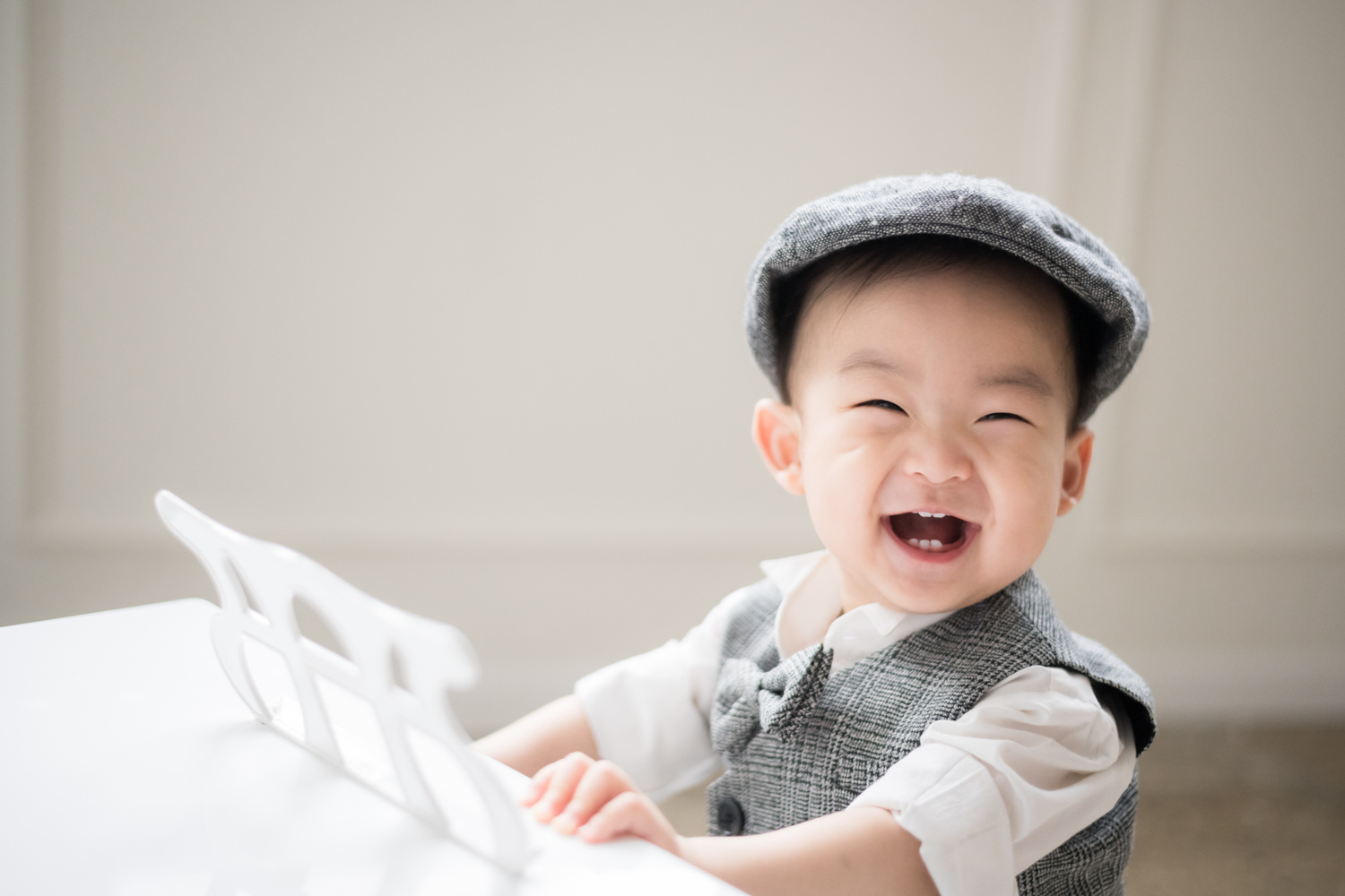 Toddler smiles from miniature piano during baby photo session.
