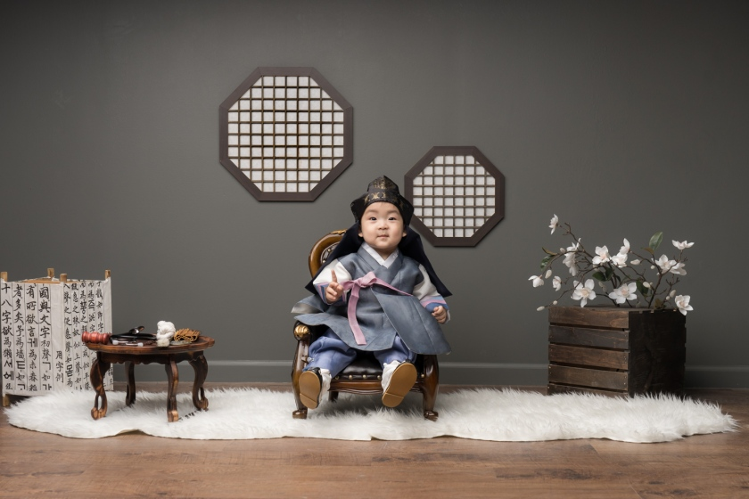Baby boy smiles in Korean outfit during Korean baby photoshoot in Chicago.