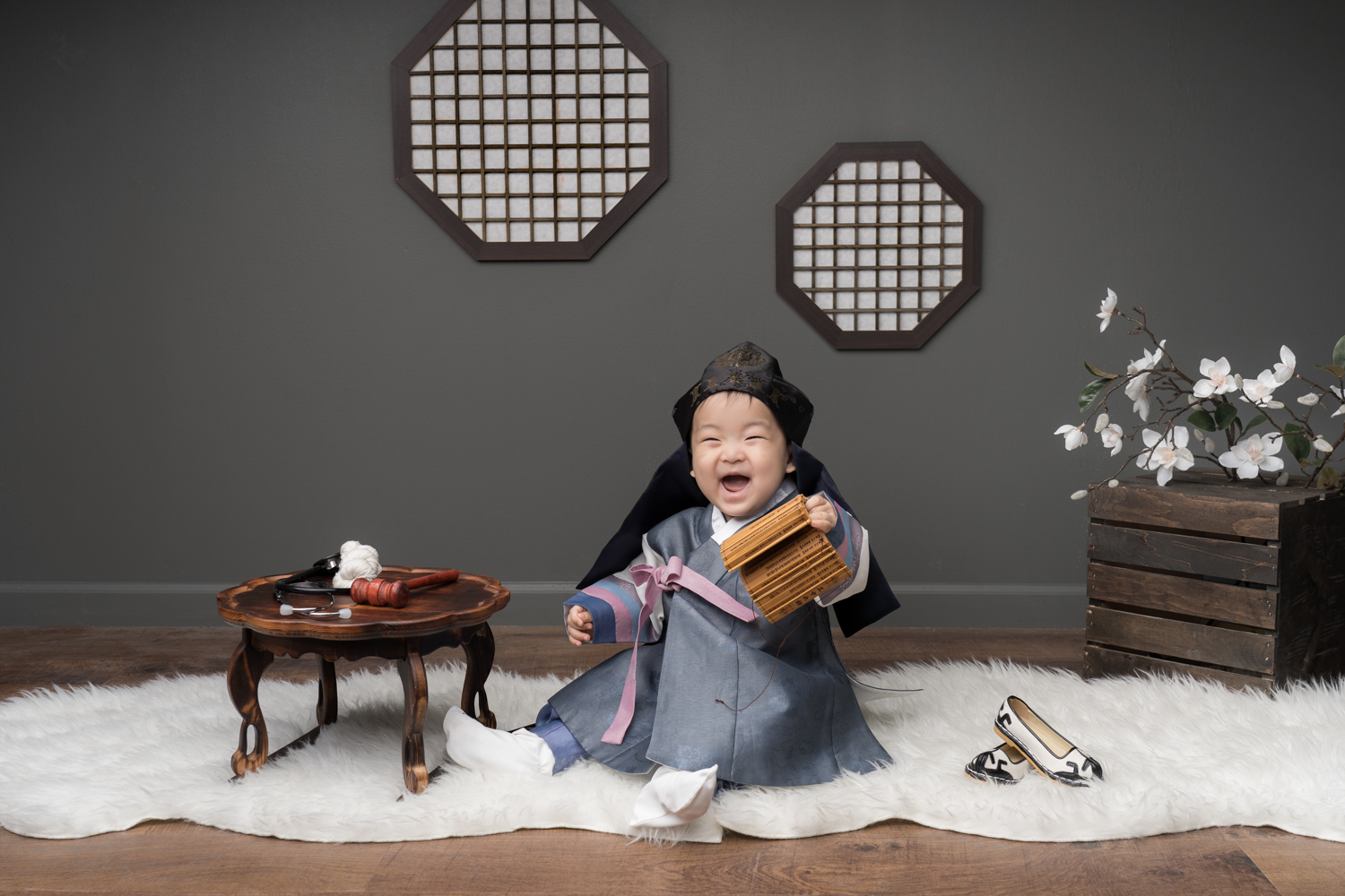 Baby boy grins during Korean baby photoshoot in Chicago.