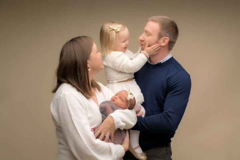A little girl holds her dads face while her family poses for a portrait.