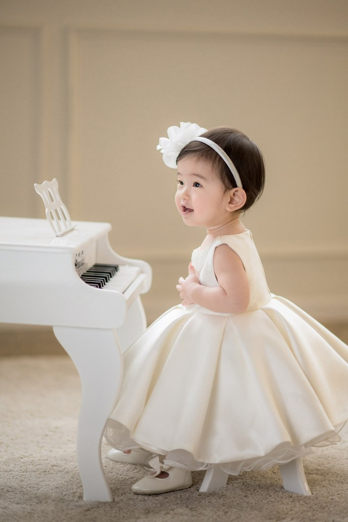 Beautiful Baby Playing with miniature white Piano