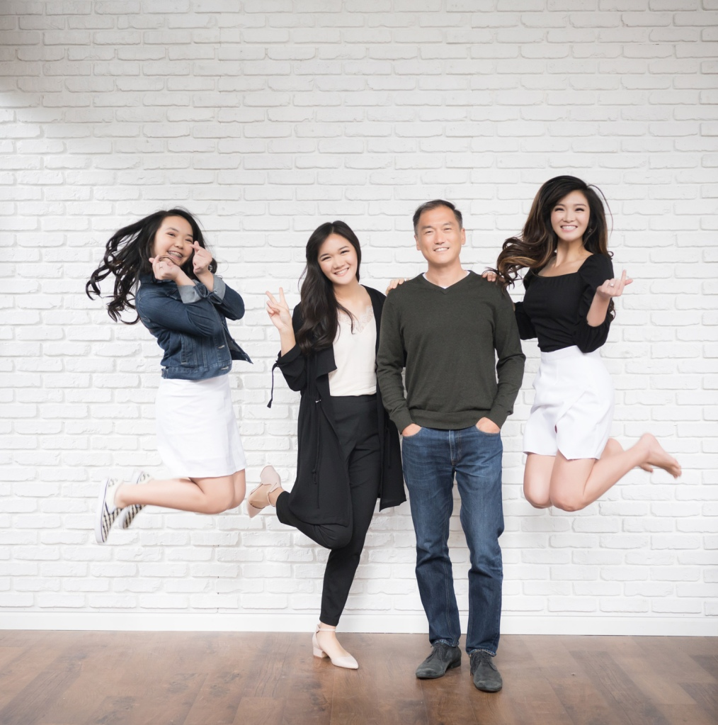 Audry's sisters jump while the three girls pose for a photo with their dad.