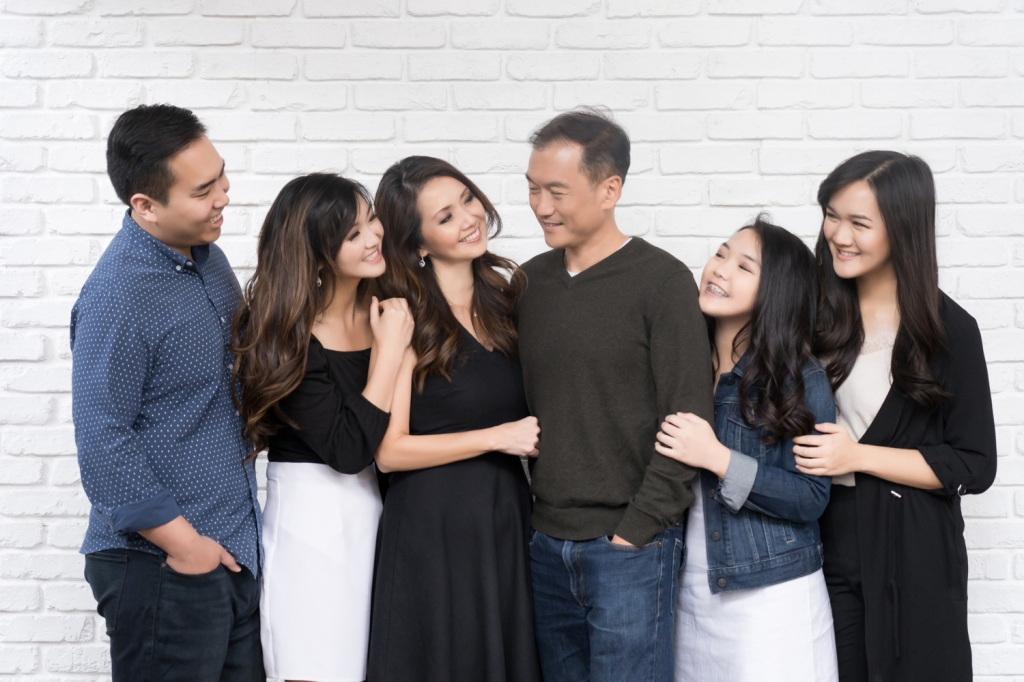 The family hugs and smiles at each other.