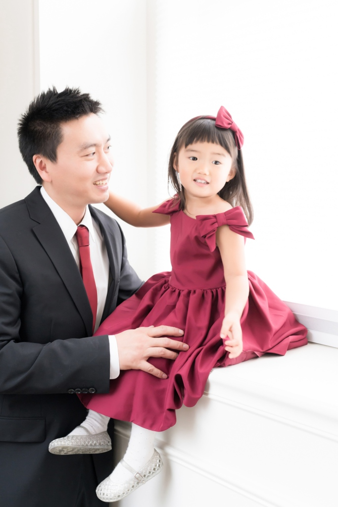 A father holds his daughter on a windowsill as she grins during a father daughter photoshoot.