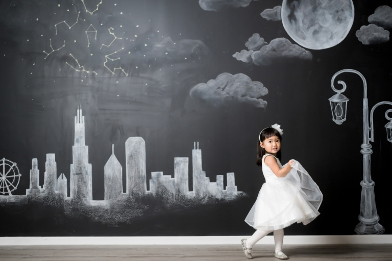 Hyorin holds her dress and dances in front of a chalk Chicago skyline mural.