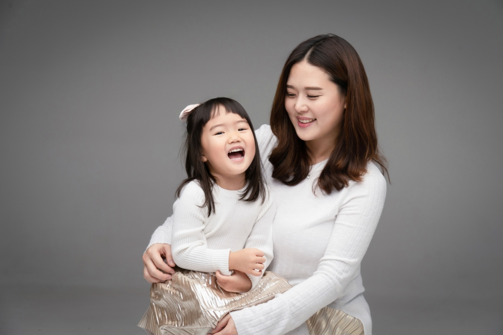 Daughter laughs with mom during a mother daughter photoshoot.