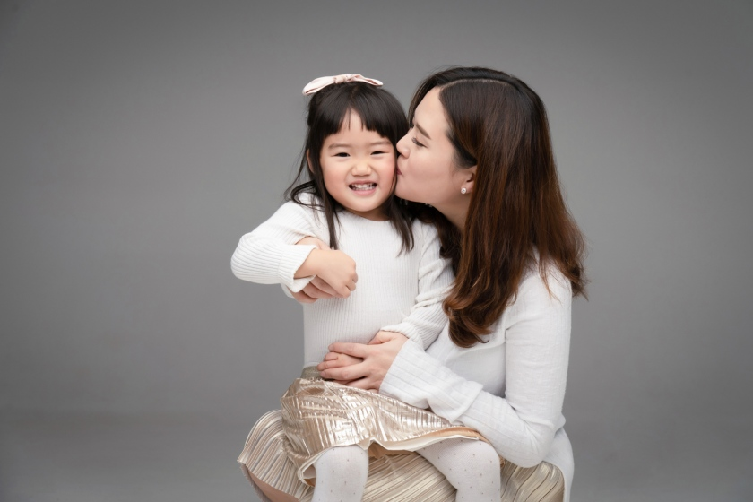 Janice kisses her daughter while holding her during a family photoshoot.