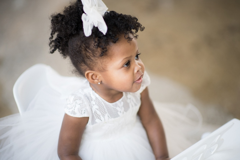 Chicago toddler sits in a white dress and looks at her parents during a photo session.