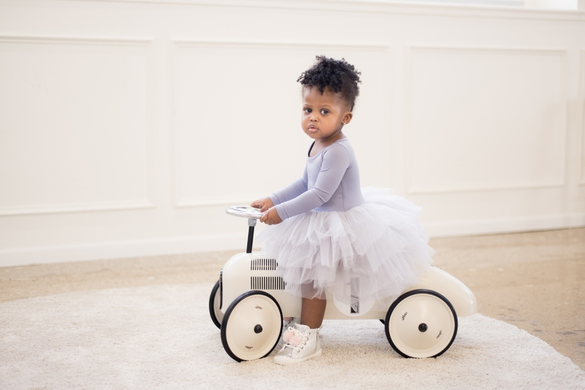 Sophia rides an antique miniature car in a grey tutu.