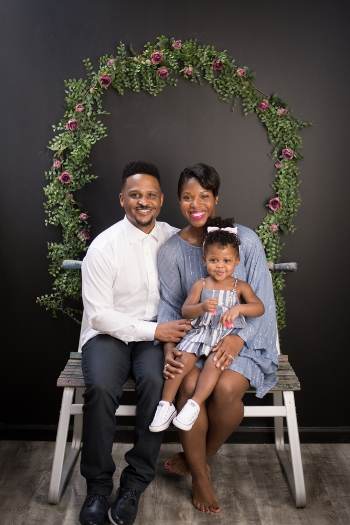 A Chicago family smiles in front of a wreath during a photo session.