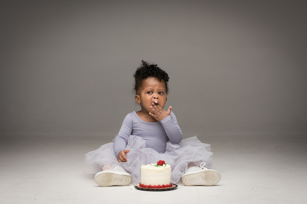 A Chicago toddler digs into a mini birthday cake in a grey tutu.