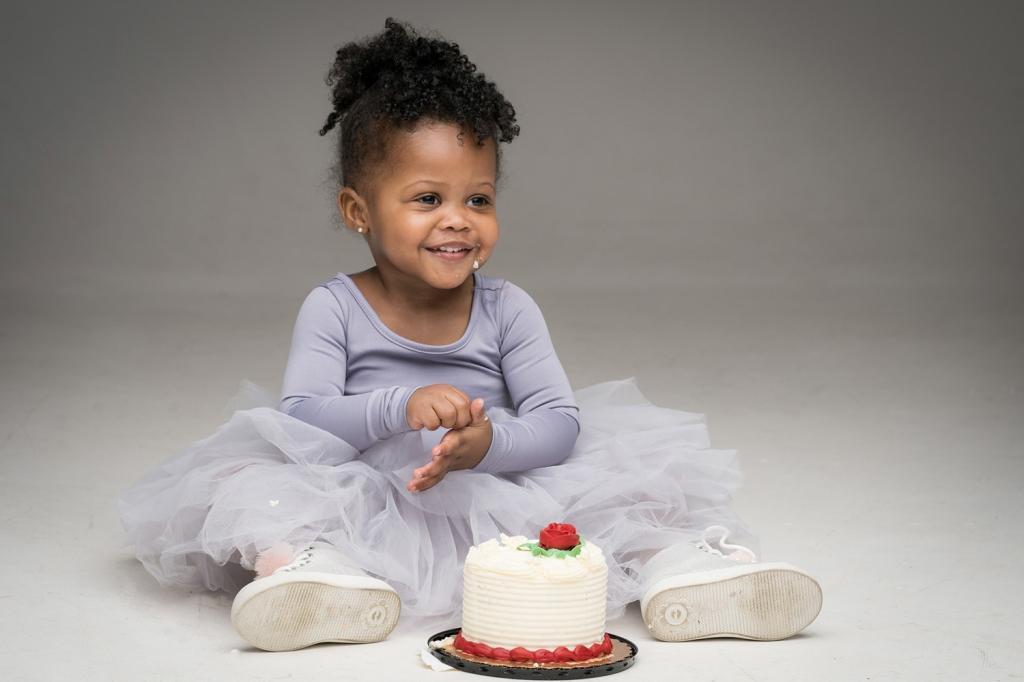 Sophia smiles while eating her mini birthday cake.