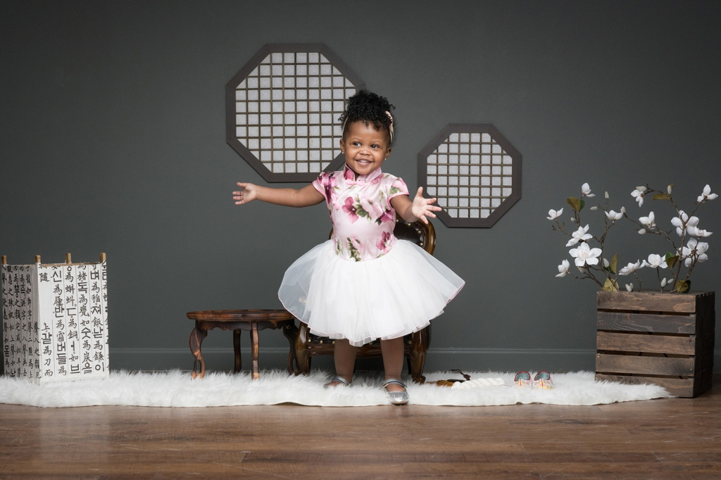 Sophia dances and smiles during a family photoshoot in Chicago.